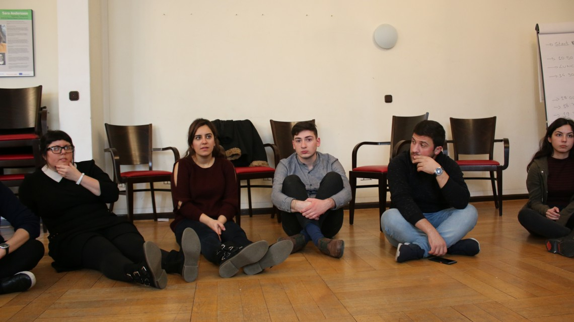 учасники сидять на підлозі