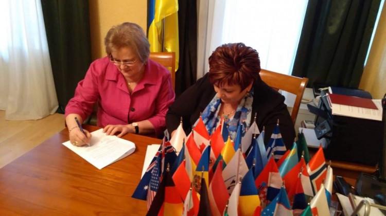 Анна Кисіль та Ірина Ключковська підписують меморандум за столом з прапорцями