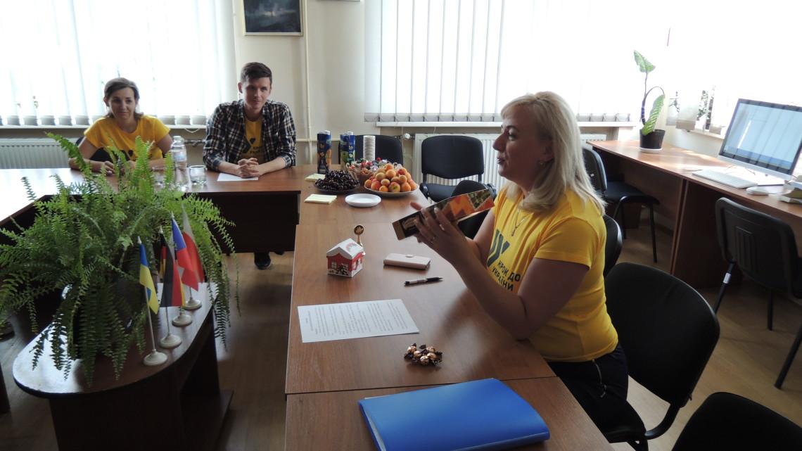 """Оксана Горда вручає учаснику Літньої школи настільну гру """"Мандрівка Україною"""""""